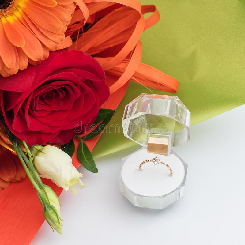 在一个礼物盒的定婚戒指有花明亮的花束的  结婚的提议 礼物为圣华伦泰` s天 图库摄影