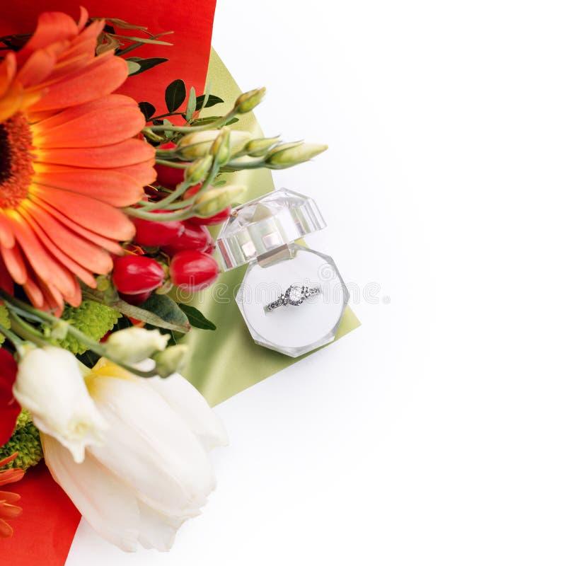 在一个礼物盒的定婚戒指有花明亮的花束的  结婚的提议 礼物为圣华伦泰` s天 免版税图库摄影