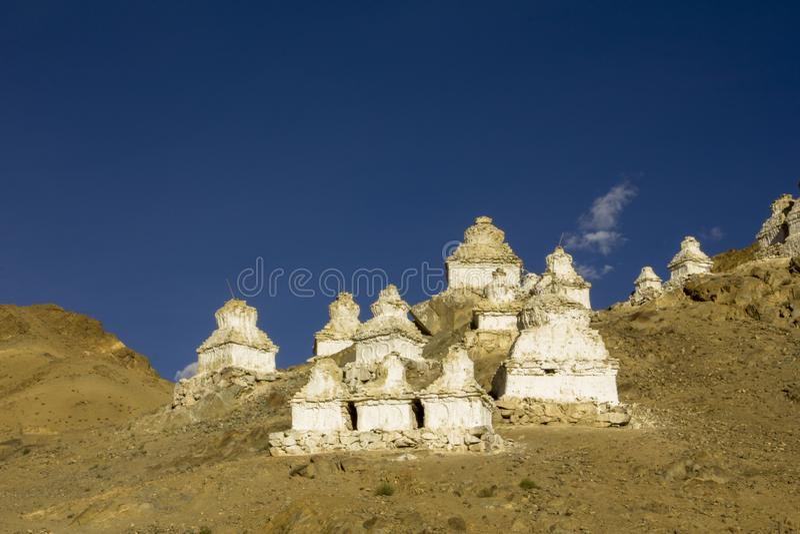 在一个离开的山坡的白色西藏佛教stupas反对天空蔚蓝和云彩 佛教圣洁寺庙 免版税库存照片