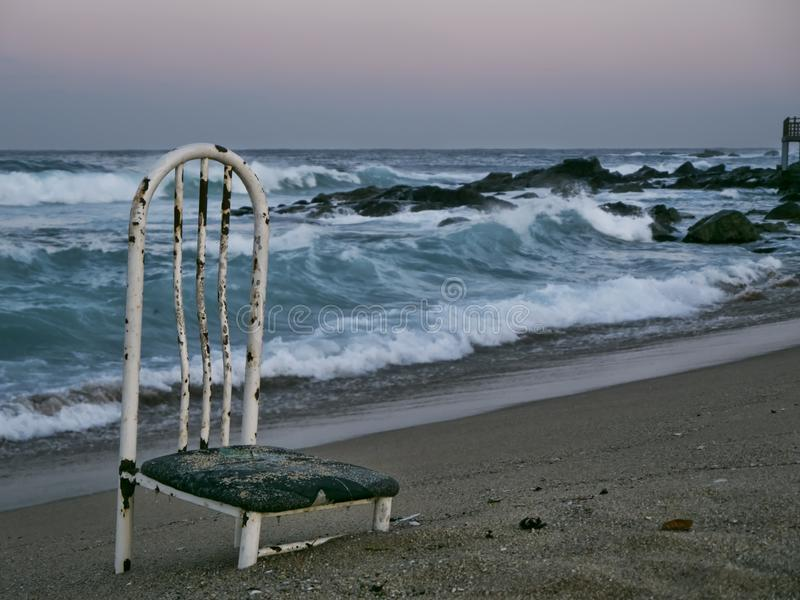 在一个离开的海滩的老椅子 免版税库存照片