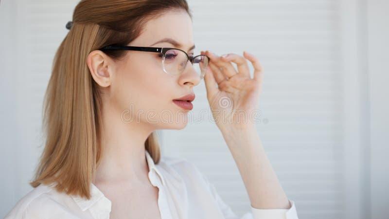 在一个稀薄的框架,视觉更正的时髦的玻璃 年轻女人的画象 免版税库存图片
