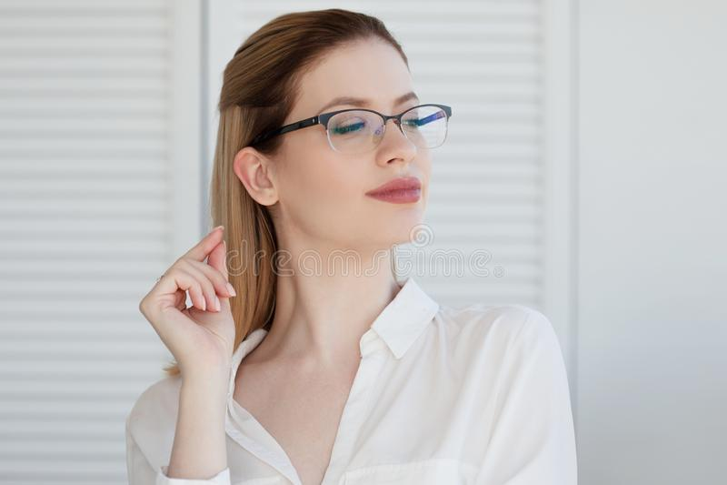 在一个稀薄的框架,视觉更正的时髦的玻璃 年轻女人的画象 免版税库存照片