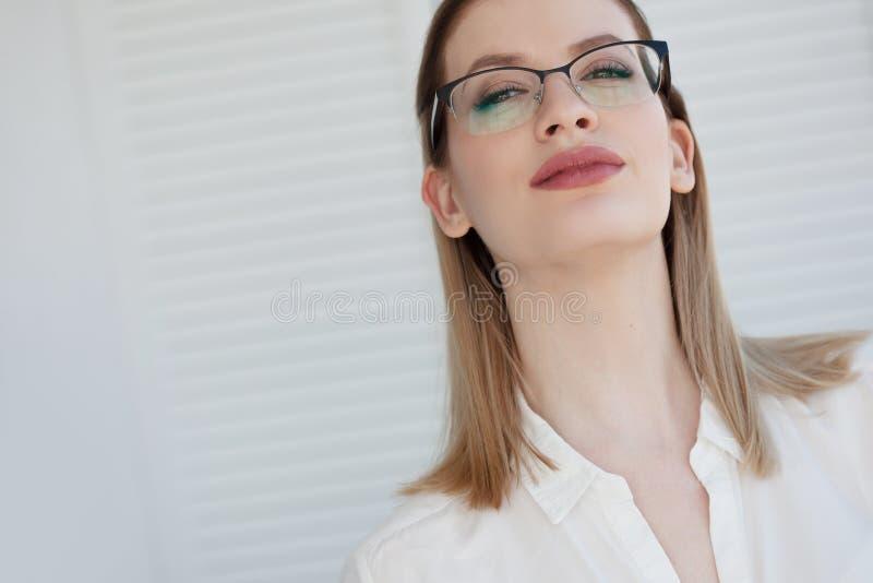 在一个稀薄的框架,视觉更正的时髦的玻璃 年轻女人的画象 免版税图库摄影
