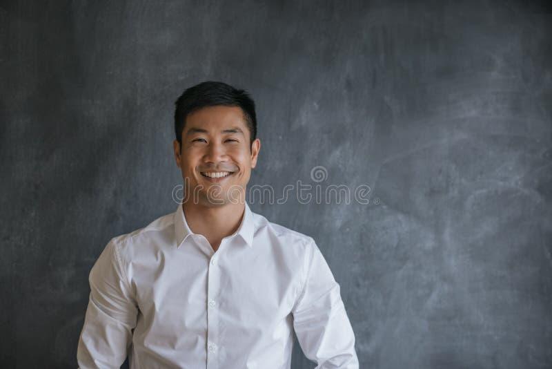 在一个空白的黑板前面的微笑的亚洲商人身分 免版税库存照片
