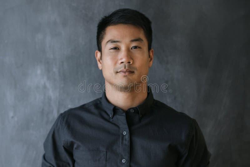 在一个空白的黑板前面的美满的亚洲商人身分 库存照片