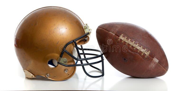 在一个空白背景的减速火箭的金子橄榄球盔和橄榄球 免版税库存照片