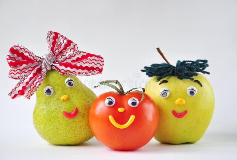 在一个空白背景的滑稽的蕃茄、苹果和梨 库存照片