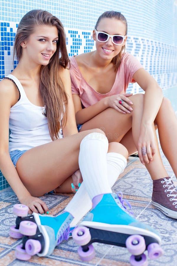 在一个空的池的楼层上的二个美丽的女孩 免版税库存照片