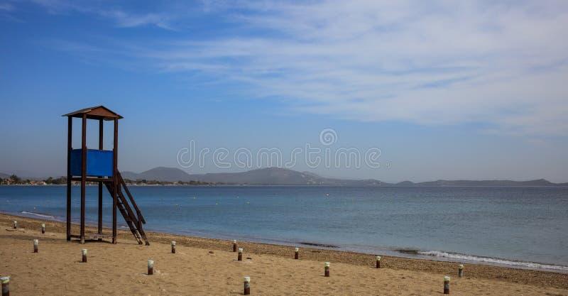在一个空的沙滩的救生员小屋 蓝天和风平浪静背景 免版税图库摄影