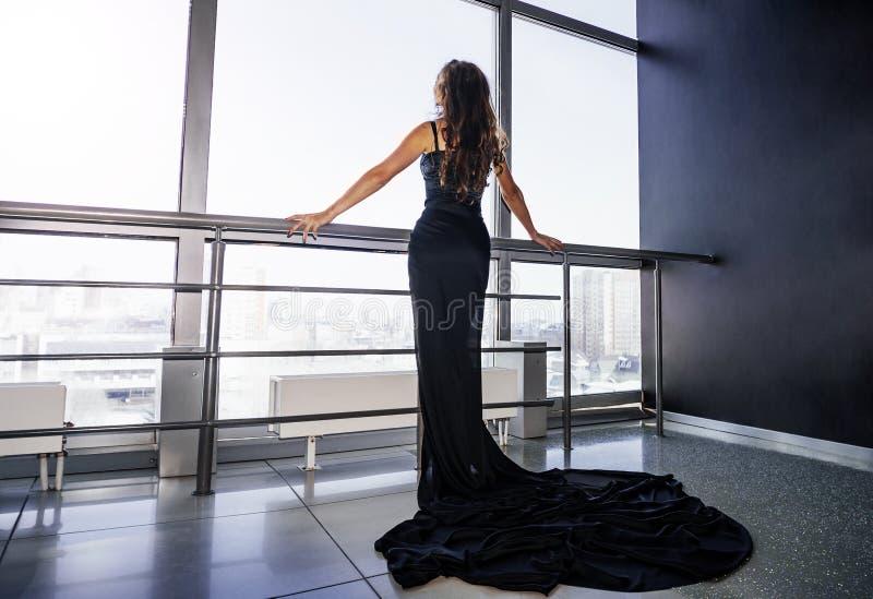 在一个窗口附近的时髦的美丽的年轻深色的妇女,在黑礼服 见面新的天,享受早晨在度假 图库摄影
