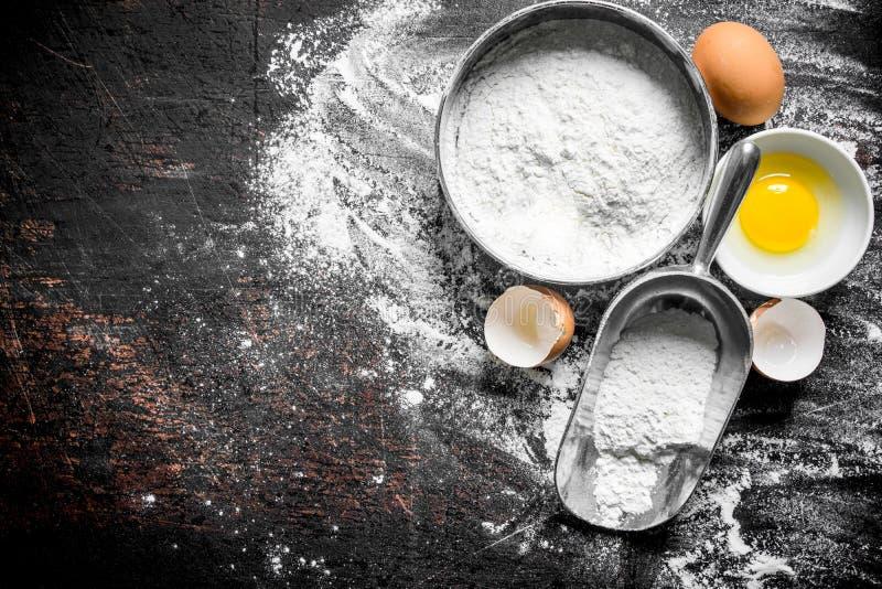 在一个筛子和一个瓢的面粉用鸡蛋 库存照片