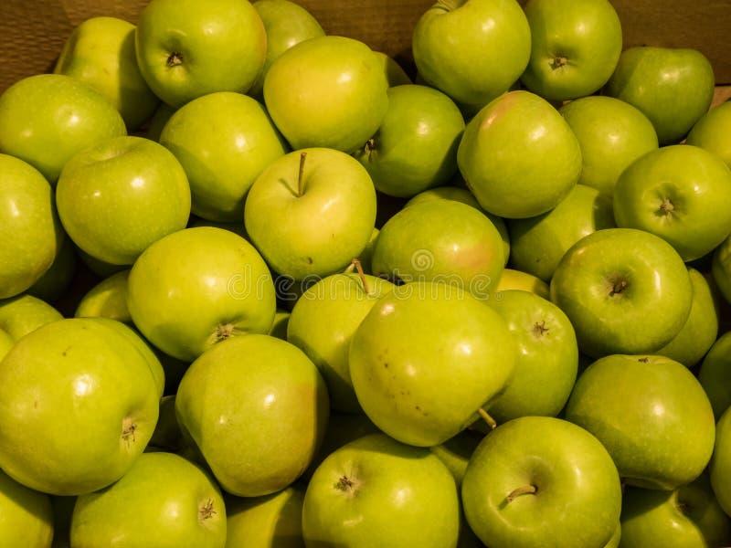 在一个箱子的许多绿色美味苹果在商店 免版税库存照片