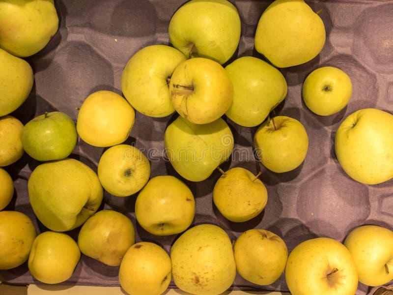 在一个箱子的许多黄色美味苹果在商店 库存照片