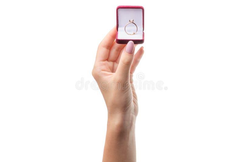 在一个箱子的金戒指在一只女性手上 库存图片