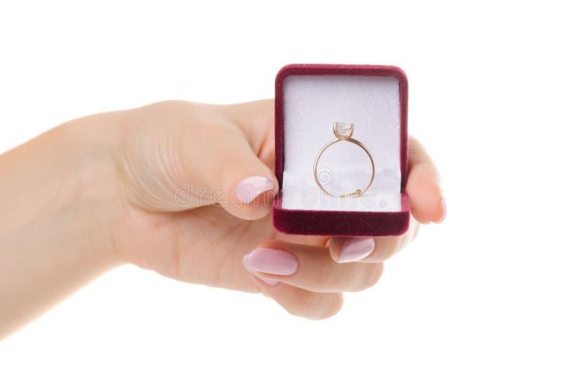 在一个箱子的金戒指在一只女性手上 库存照片