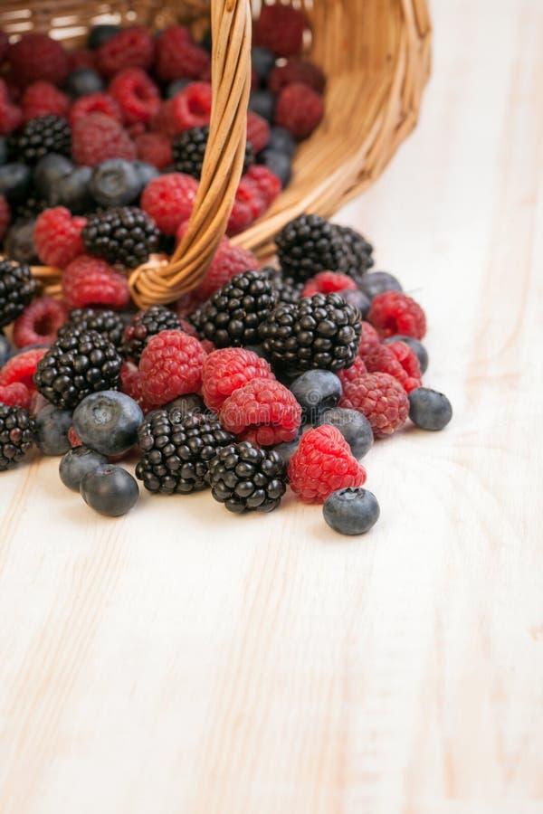 在一个篮子的不同的莓果在一张木桌上 库存图片