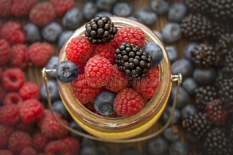 在一个篮子的不同的莓果在一张木桌上 图库摄影