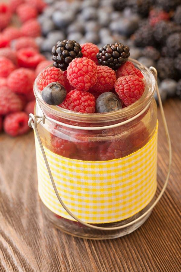 在一个篮子的不同的莓果在一张木桌上 库存照片