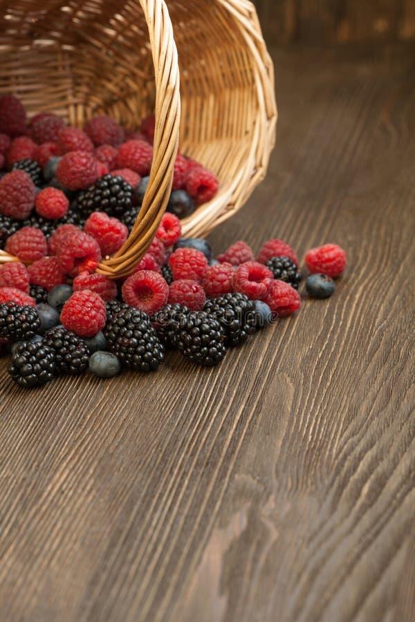 在一个篮子的不同的莓果在一张木桌上 免版税库存照片
