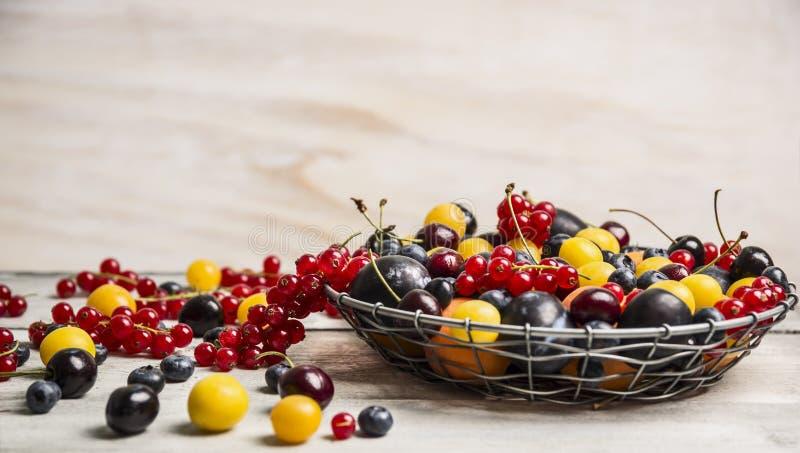 在一个篮子的不同的莓果在一张白色木桌上 库存图片