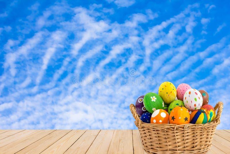 在一个篮子的五颜六色的复活节彩蛋在蓝天bac的木纹理 库存图片