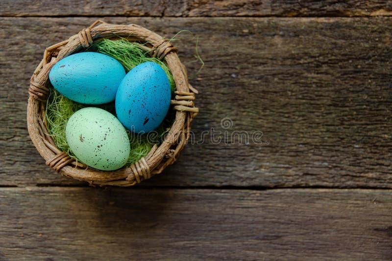 在一个篮子的复活节彩蛋在木背景 库存照片