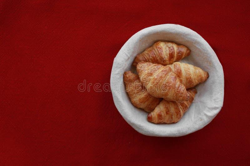 在一个篮子的新近地被烘烤的新月形面包在红色 免版税图库摄影