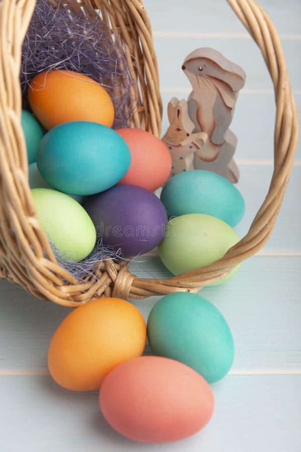 在一个篮子的被洗染的明亮的复活节彩蛋与五颜六色的蓝色西沙尔麻和木兔宝宝 免版税库存图片