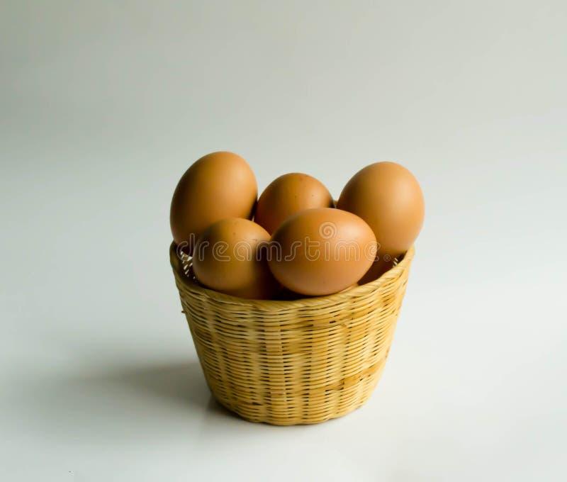 在一个篮子的鸡蛋在白色黑地面 免版税库存照片