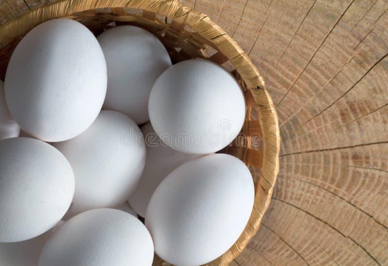 在一个篮子的鸡鸡蛋在木背景,特写镜头 免版税库存图片