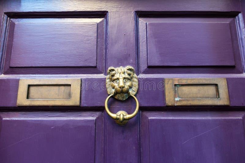 在一个紫色门的一个黄铜通道门环 免版税库存图片