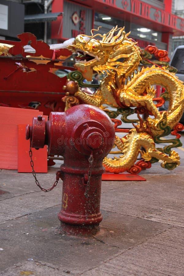 在一个红火消防栓后的金黄中国龙在九龙香港 免版税库存照片