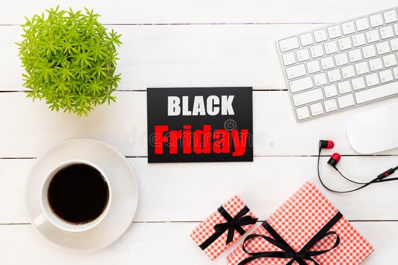 在一个红色和黑标记的黑星期五销售文本与咖啡杯、植物桌、礼物盒耳机和老鼠键盘在白色木 免版税库存照片