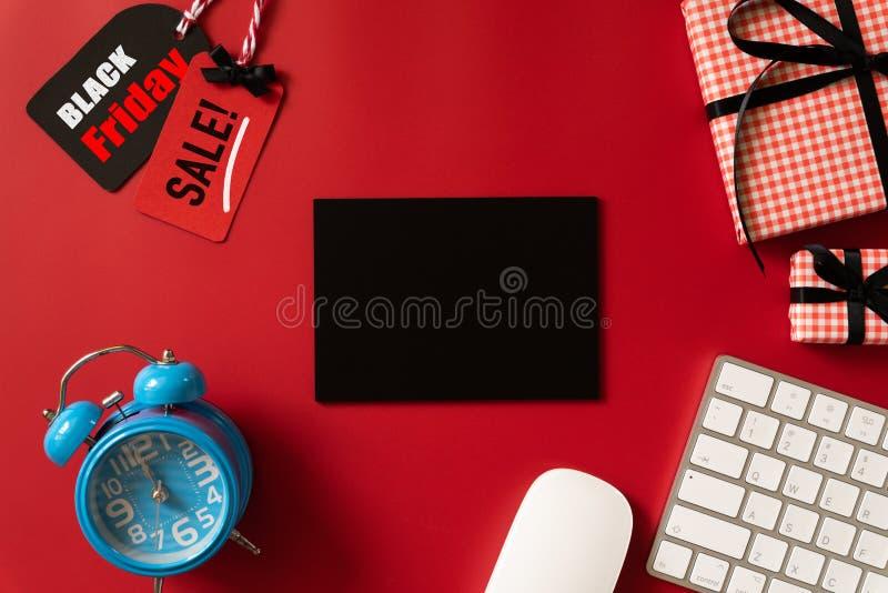 在一个红色和黑标记的黑星期五销售文本与闹钟、键盘计算机和礼物盒在红色背景 免版税库存图片