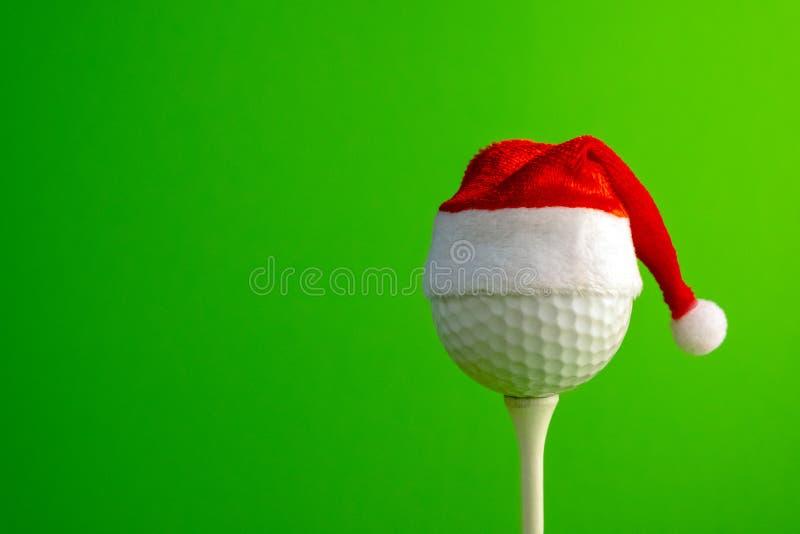 在一个红色圣诞老人项目帽子的高尔夫球在发球区域登上了 在圣诞节和新年题材的体育概念  绿色背景 复制 库存照片