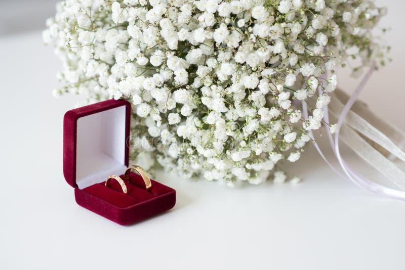 在一个红色天鹅绒箱子和新娘花束的结婚戒指在一张白色桌 免版税库存照片