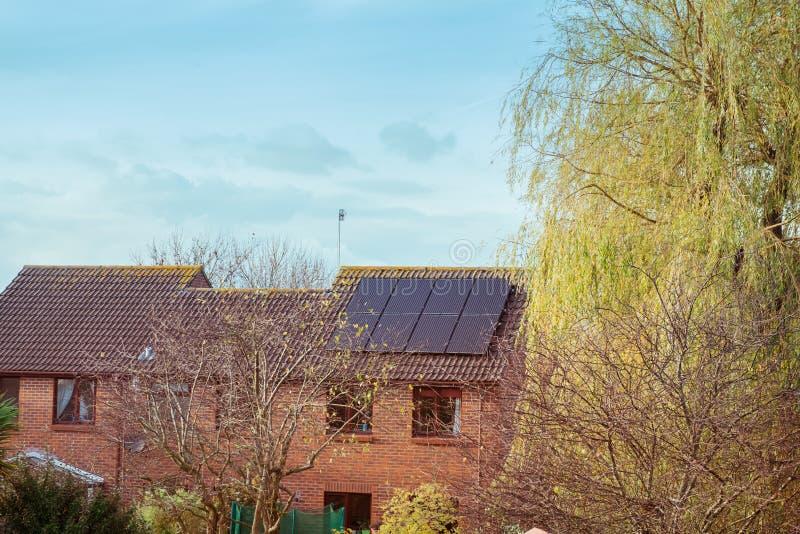 在一个红色屋顶房子、树和天空蔚蓝的太阳电池板 供选择的绿色能量概念 选择聚焦,拷贝空间 免版税库存图片