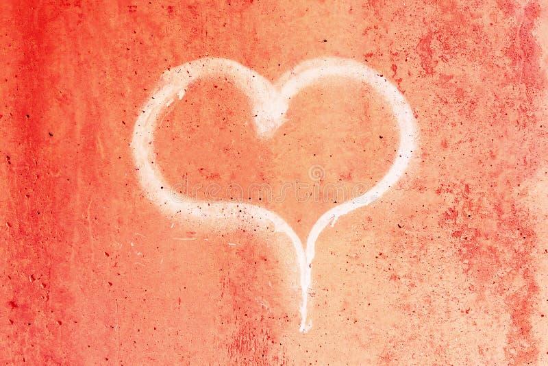 在一个红色混凝土墙上的白垩画的心脏 免版税库存照片