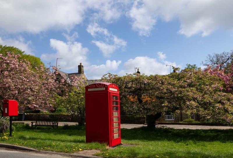 在一个红色电话亭旁边的小岗位箱子 库存照片