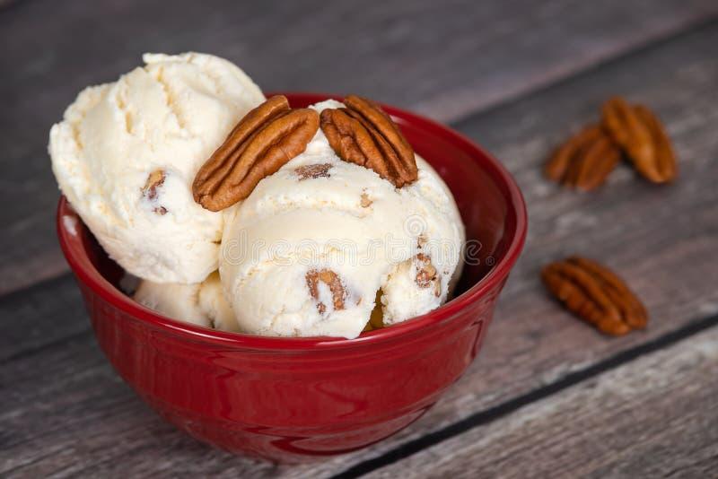 在一个红色碗的胡桃冰淇淋涂黄油 免版税库存图片