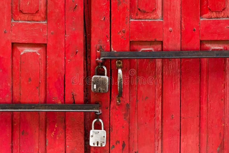 在一个红色门的两把锁 库存图片