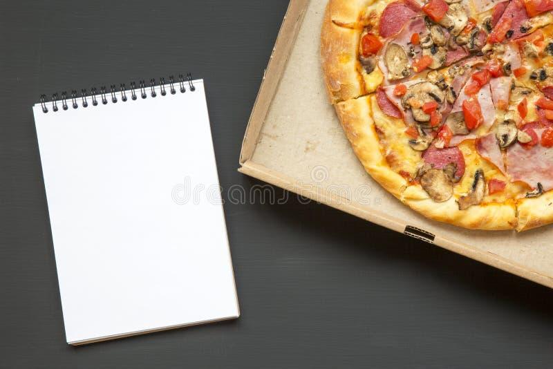 在一个纸板箱的新鲜的薄饼有在黑暗的背景,顶视图的笔记本的 复制空间 免版税库存图片