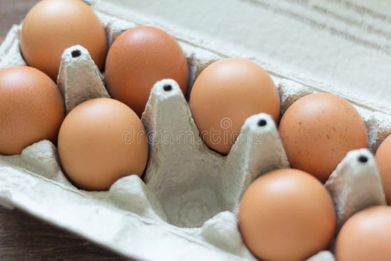 在一个纸板箱的鸡鸡蛋,有一个空的细胞的 库存图片