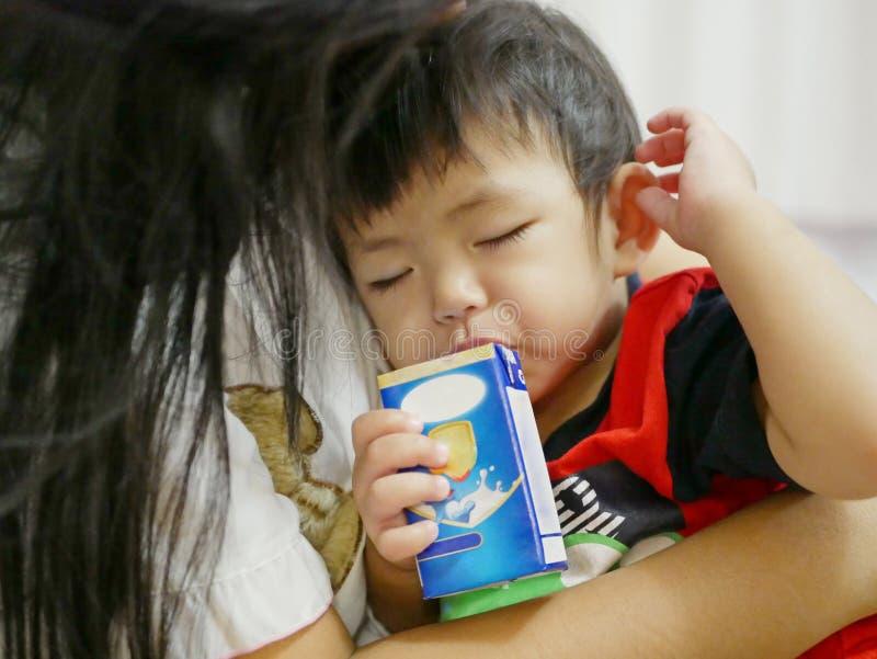 在一个纸盒外面的困亚洲女婴饮用奶有秸杆的 库存照片