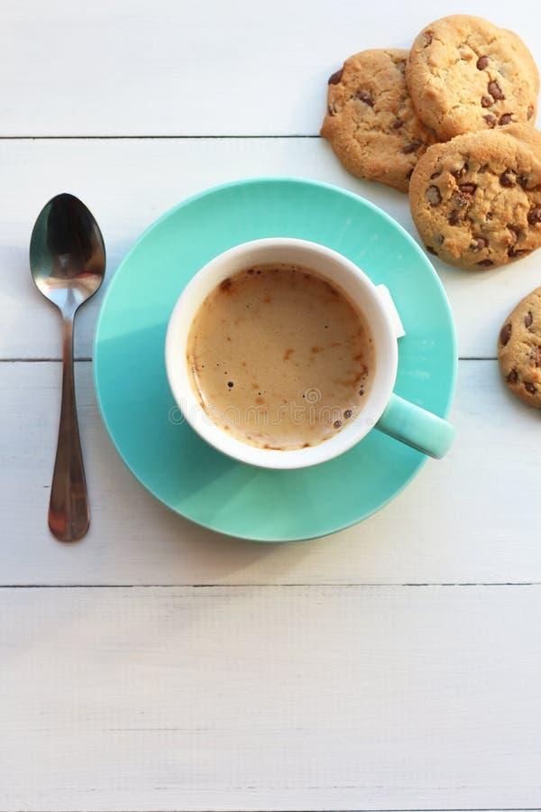 在一个绿松石杯子和曲奇饼的咖啡在一张白色桌上顶视图 免版税库存照片