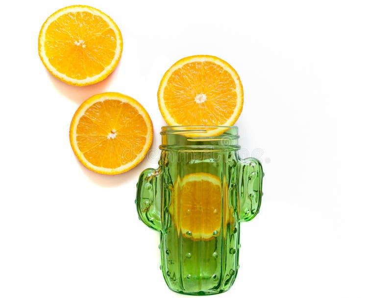 在一个绿色瓶子的橙色切片鸡尾酒和圆滑的人的 饮料的玻璃瓶子与在白色背景的秸杆 明亮的夏天mo 免版税图库摄影