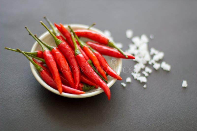 在一个绿色碗的红色小辣胡椒有盐水晶的附近在黑背景 E 库存图片