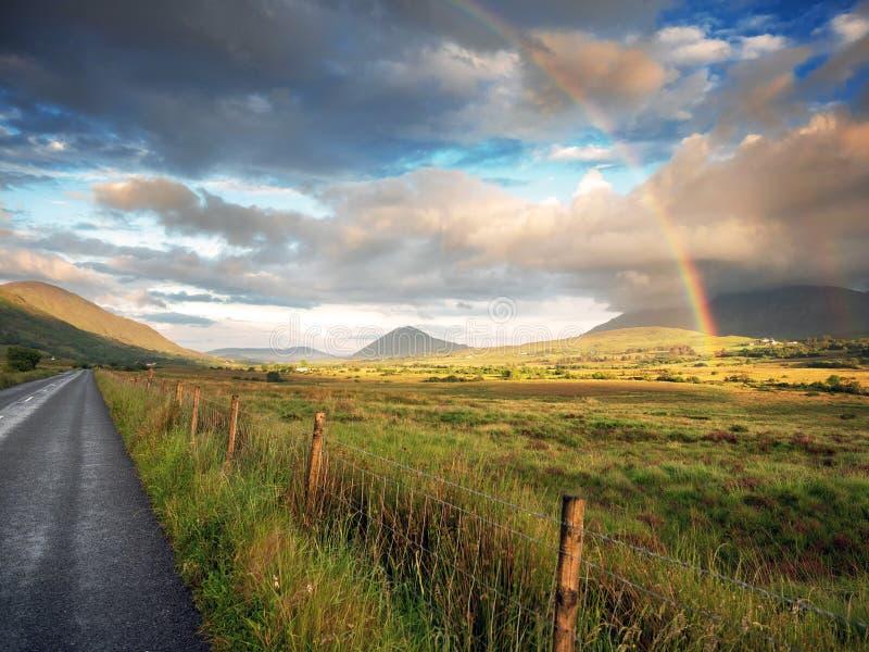 在一个绿色领域的五颜六色的彩虹,美丽的富有的天空,康尼马拉圈,爱尔兰 库存图片