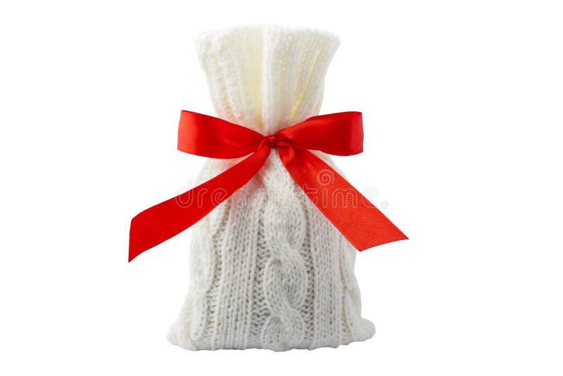 在一个编织的袋子的礼物与一条红色丝带 在一个空白背景 免版税库存图片