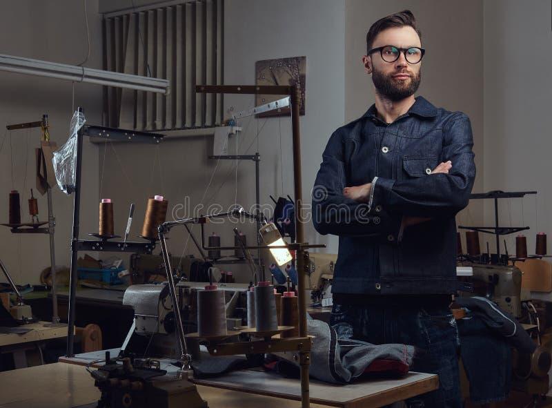 在一个缝合的车间剪裁与缝纫机的常设近的桌和看一台照相机 免版税库存照片